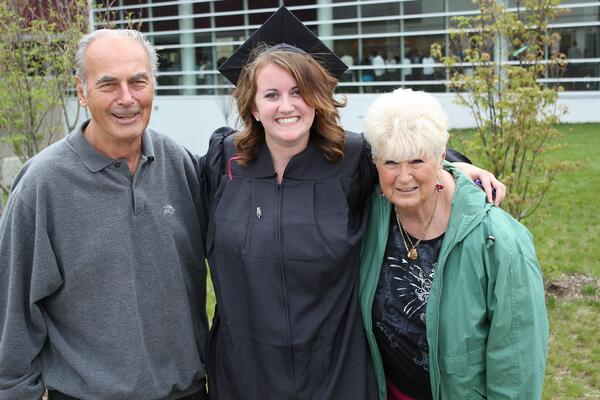 Three people standing outside; the person in the middle is wearing a cap & gown